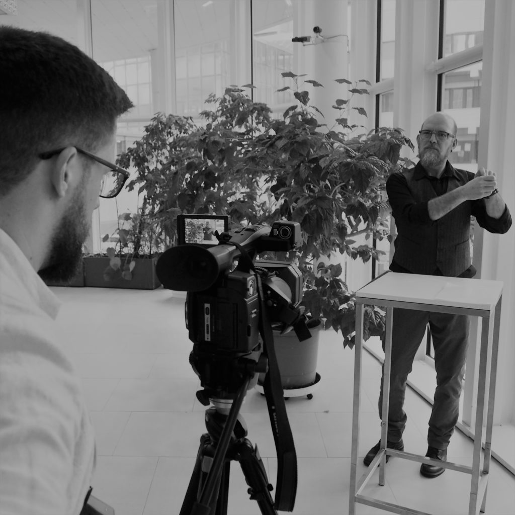 Filming for a career guidance video about Deaf interpreters. One man looks into the screen of a camera on a tripod, filming an iterview with another man who is signing his responses.